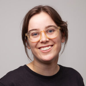 Chris Ebbs looks towards the camera and smiles. She is wearing a plain black shirt and glasses.
