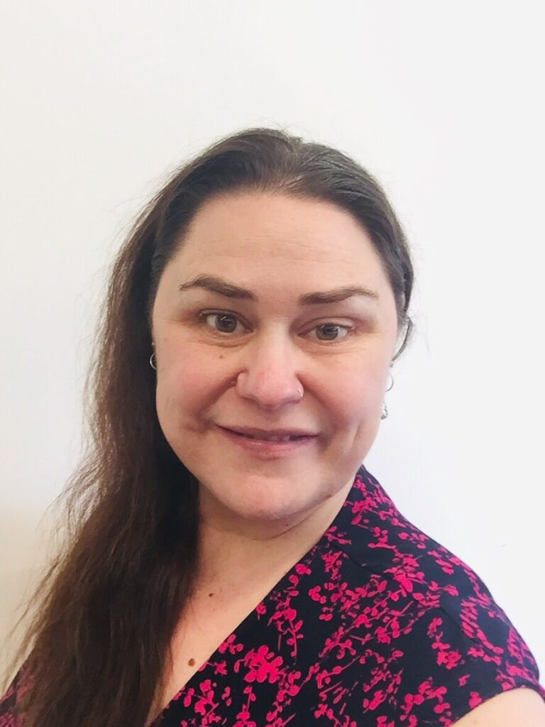A picture of Jocelyn Hargrave. She is looking at the camera, has pale skin and long brown hair parted over one shoulder. She is wearing a fun pink and black patterned top.